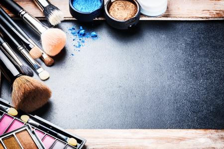 maquillaje de ojos: Varios productos de maquillaje sobre fondo oscuro con copyspace