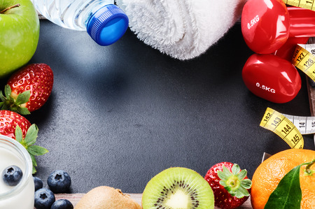 Fitness frame with dumbbells, towel and fresh fruits. Copy space photo