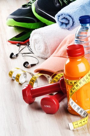 body toning: Fitness concept with dumbbells, fruits juice and sportswear. Workout setting