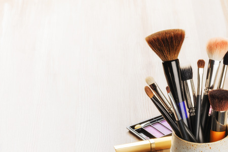 Various makeup brushes on light background with copyspace