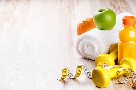 salud y deporte: Concepto de fitness con pesas y frutas frescas. Ajuste de Entrenamiento