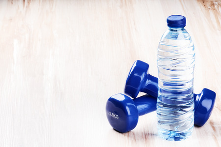 dumbbell: Fitness concept with dumbbells and bottle of water. Copy space Stock Photo
