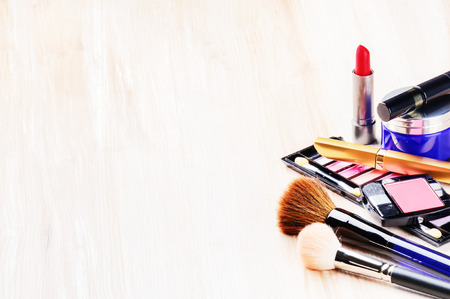 up: Various makeup products on light background with copyspace