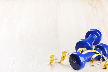 Fitness concept with dumbbells and measuring tape