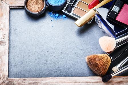 mujer maquillandose: Varios productos de maquillaje sobre fondo oscuro con copyspace