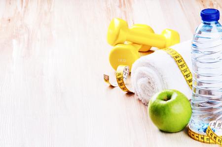 concept de remise en forme avec des haltères, vert pomme et une bouteille d'eau. Espace texte