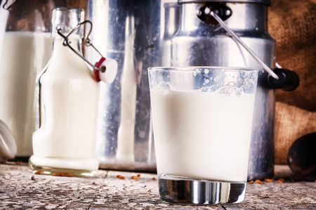 Glass of fresh milk in country setting. Closeup shot Stock Photo