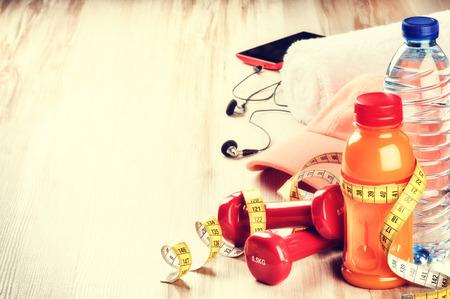 Fitness concept with dumbbells, fruits juice, water and sportswear