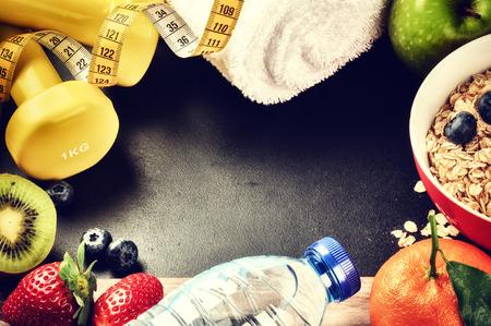 fitness: Marco de la aptitud con pesas, botella de agua y fruta fresca. Concepto de estilo de vida saludable con espacio de copia Foto de archivo