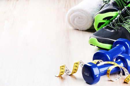 Fitness concept with dumbbells,  sneakers and measuring tape