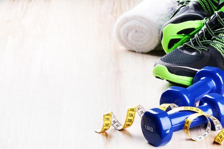 salud y deporte: Concepto de fitness con pesas, zapatillas de deporte y cinta métrica
