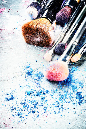 Makeup brushes and crushed eyeshadow on dark background