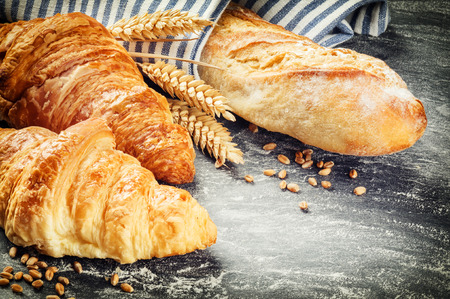 croissant: Freshly baked baguette and croissants in rustic setting with copyspace