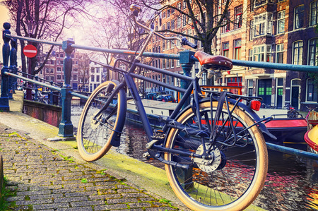 Old bicycle standing next to canal. Amsterdam cityscape 스톡 콘텐츠