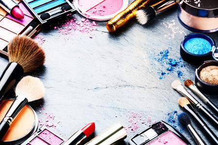 mujer maquillandose: Marco colorido con varios productos de maquillaje sobre fondo oscuro Foto de archivo