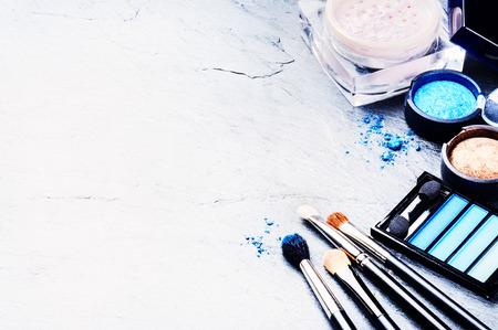 mujer maquillandose: Varios productos de maquillaje en tono azul con copyspace Foto de archivo