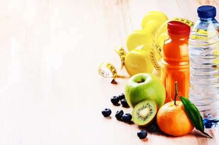 Fitness concept with dumbbells and fresh fruits. Copy space Standard-Bild