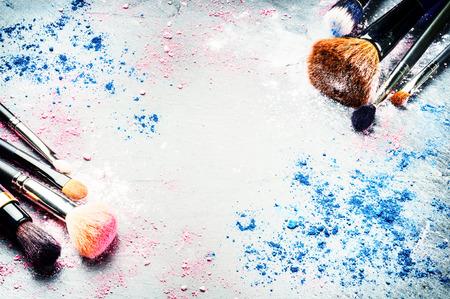 Pinceaux de maquillage et des fards à paupières écrasées sur fond sombre Banque d'images