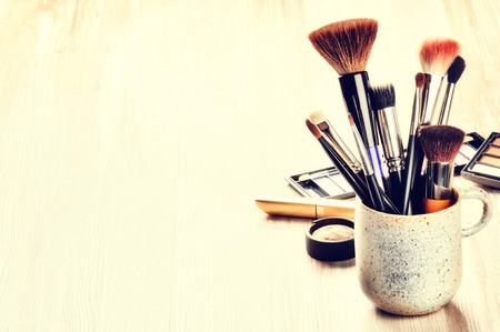 makeup fashion: Various makeup brushes on light background with copyspace