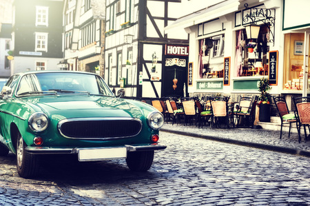 Retro car parked in old European city street. Copy space Stock Photo