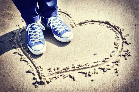 beach feet: Romantic setting with heart sign on the beach. Copyspace