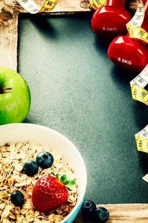 Fitness frame met halters en gezond voedsel. Kopieer de ruimte