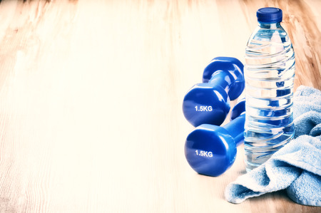 fitness: Fitness concept with dumbbells and water bottle. After workout setting Stock Photo
