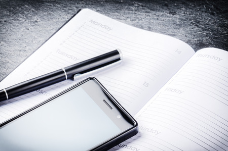 Business concept with agenda, mobile phone and pen. Copy space