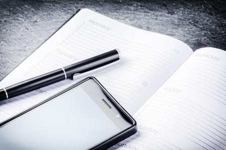 Zakelijk concept met agenda, mobiele telefoon en pen. Kopieer de ruimte Stockfoto