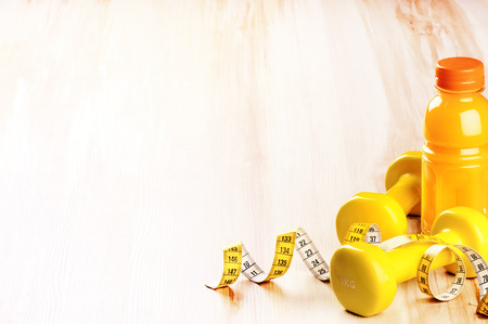 Fitness concept with dumbbells and fresh fruit juice in yellow tone