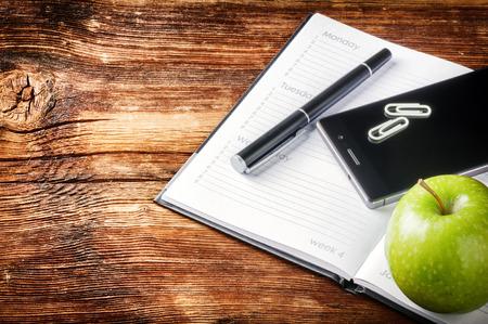 Desktop met papieren agenda, smartphone en groene appel. Kantoor achtergrond