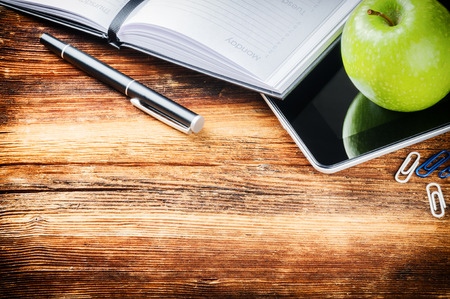 meeting agenda: Wooden desktop with paper agenda, digital tablet and green apple Stock Photo