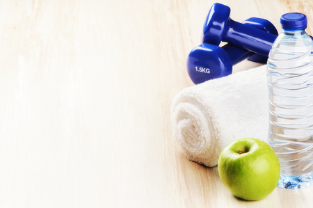 Fitness concept with dumbbells, green apple and water bottle. Copy space