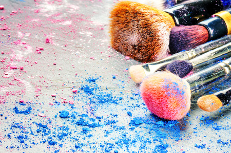 Makeup brushes and crushed eyeshadow. Copy space