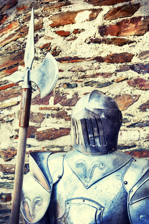 halberd: Metal knights armor on ancient stone wall background Stock Photo