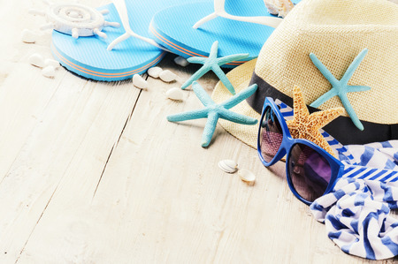 Summer holiday setting with straw hat and flip flops. Copy space