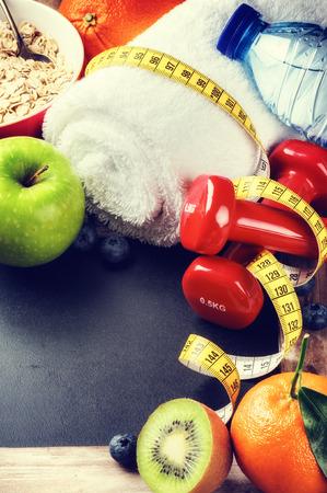 아령, 물 병, 신선한 과일과 함께 피트니스 프레임입니다. 복사 공간 건강한 라이프 스타일 개념
