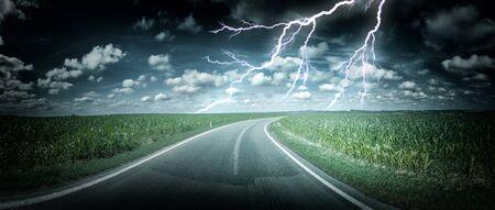 champ de mais: Paysage panoramique avec orage au-dessus route de campagne. Nature background