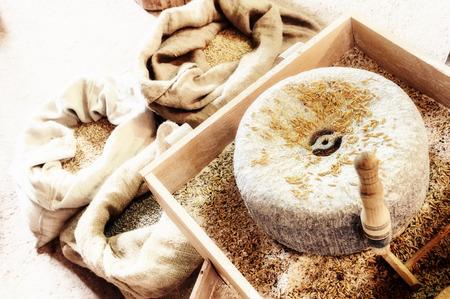 millstone: Ancient millstone with wheat grains. Closeup shot