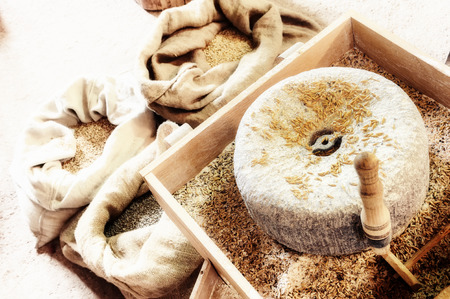 Ancient millstone with wheat grains. Closeup shot