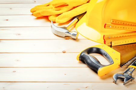 Hard hat and various tools on wooden background. Construction concept
