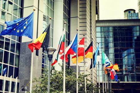the european economic community: Waving flags in front of European Parliament building. Brussels, Belgium
