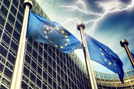 European Union flags on dark thunderstorm sky background Zdjęcie Seryjne