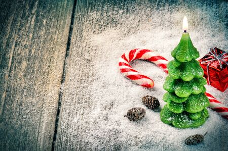 christmas candle: Festive background with Christmas tree candle and candy cane Stock Photo
