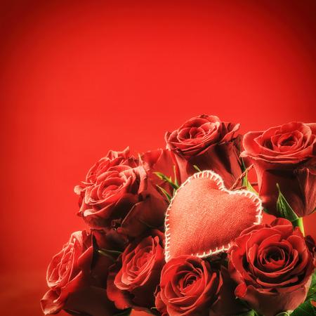 aniversario de bodas: Ramo de rosas rojas con el corazón decorativo. Concepto de San Valentín con espacio de copia