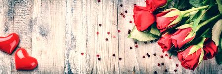 date: Blumenstrauß aus roten Rosen mit dekorativen Herz. St. Valentinstag-Konzept mit Kopie Raum