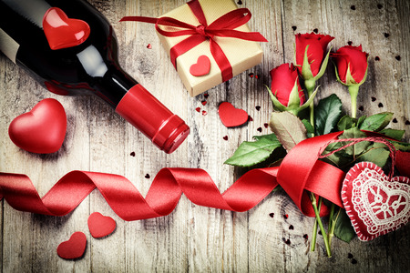 St Valentines setting with red roses bouquet, present and red wine bottle. Copy space Stock Photo