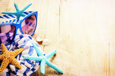 Summer holiday setting with striped scarf, sunglasses and starfishes. Copy space