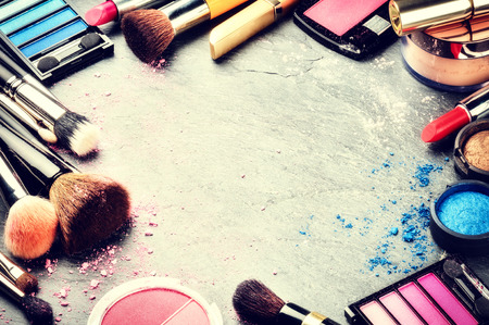 make up brush: Colorful frame with various makeup products on dark background. Copy space