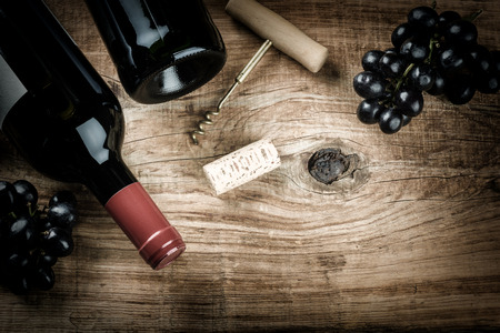 Setting with bottle of red wine, grape and corks. Wine list concept with copy space Foto de archivo
